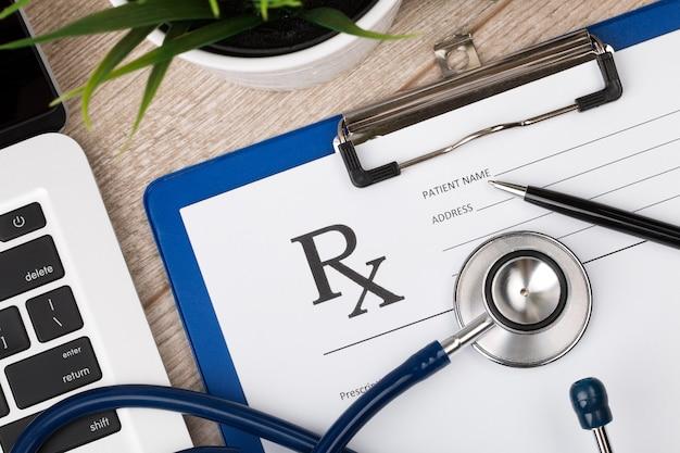 Vue rapprochée de la table de travail du médecin. stéthoscope, ordinateur portable et formulaire de prescription vierge. vue de dessus