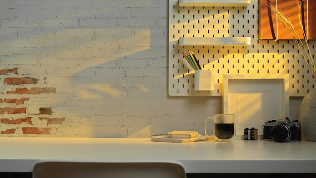 Vue rapprochée de la table de travail avec espace copie, appareil photo, papeterie et décoration au bureau à domicile