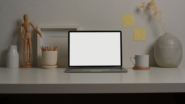 Vue rapprochée de la table de travail avec des fournitures et des décorations pour ordinateur portable dans la salle de bureau à domicile