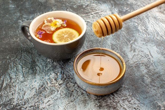 Vue rapprochée d'une tasse de thé au citron et miel sur fond gris