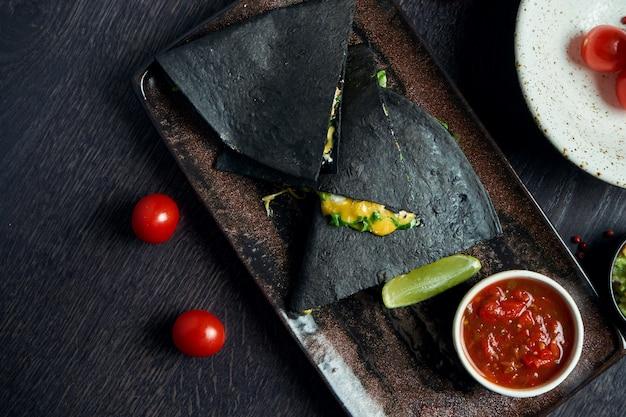Vue rapprochée de la tortilla noire quesadilla au fromage sur une plaque brune avec sauce rouge sur une surface en bois. cuisine traditionnelle mexicaine