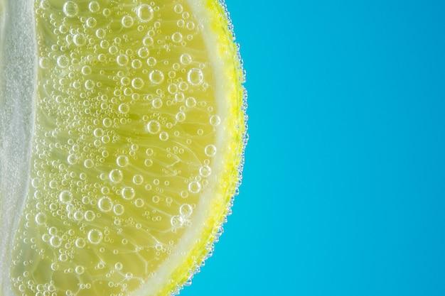 Vue rapprochée d'une tranche de citron vert dans de l'eau gazeuse avec des bulles.