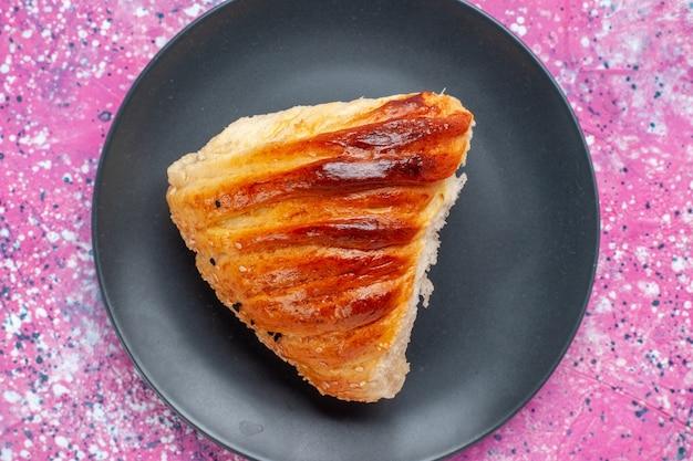 Vue rapprochée de la tranche de pâtisserie avec garniture verte à l'intérieur de la plaque sur fond rose.