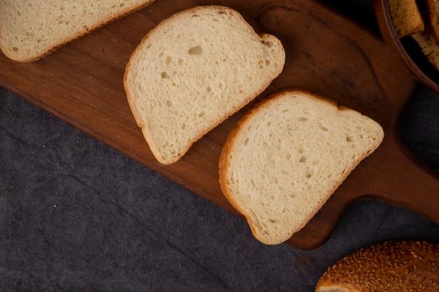 Vue rapprochée de tranches de pain blanc sur une planche à découper sur fond marron avec copie espace