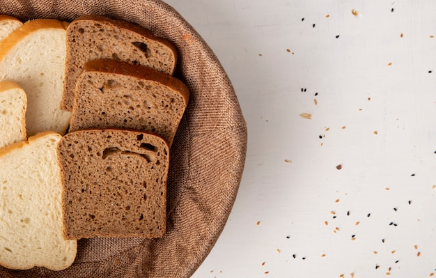 Vue rapprochée de tranches de pain blanc et de seigle dans le panier sur le côté gauche et fond blanc avec copie espace