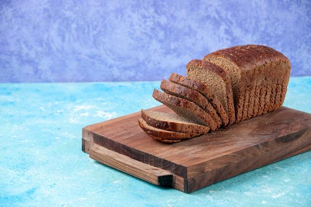 Vue rapprochée de tranches de pain noir coupées en deux sur des planches de bois sur le côté gauche sur fond bleu glace clair