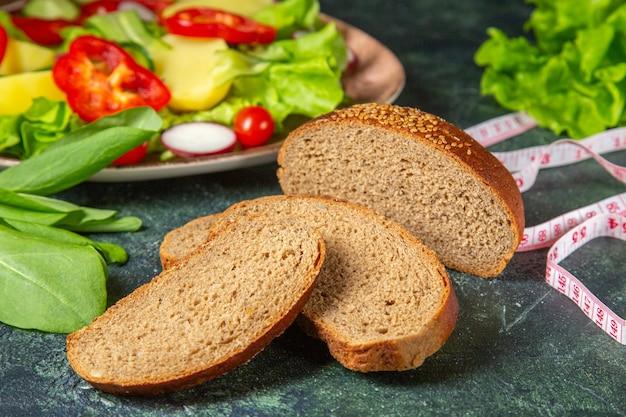 Vue rapprochée de tranches de pain noir de légumes frais hachés sur une assiette et de mètres de paquet vert sur la surface de couleurs foncées