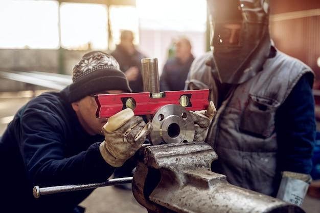 Vue rapprochée des travailleurs en uniforme de protection travaillant avec l'outil de niveau à bulle et le disque métallique sur l'outil d'étau après réparation dans l'atelier industriel.
