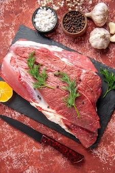 Vue rapprochée de la viande rouge fraîche avec du vert et du poivre sur un tableau noir couteau ails citron épices marteau en bois citron sur fond rouge pastel à l'huile