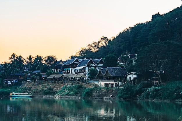 Vue rapprochée de la ville traditionnelle de la rivière lao avec architecture en bois et bateau de pêche. petit village isolé dans la jungle dense du laos.