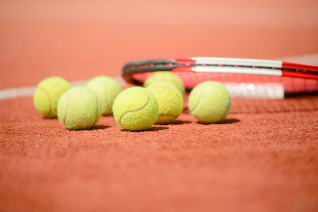 Vue de la raquette de tennis et des balles sur le court de tennis en terre battue.