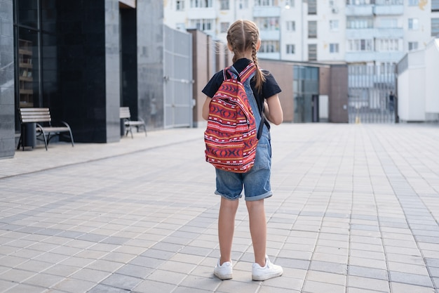Une vue rare d'une fille triste avec un sac à dos et des livres va à l'école. retour au concept de l'école.