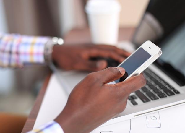 Vue recadrée d'un concepteur de sites web ux professionnel travaillant sur son nouveau projet de modèles de smartphone tout en utilisant une tablette à écran vierge