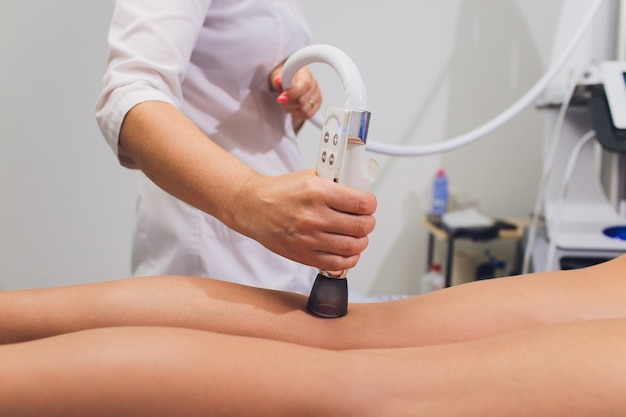 Vue recadrée de cosmétologue avec rouleau faisant le massage des fesses starvac.
