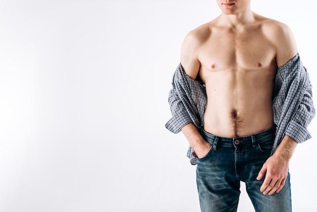 Vue recadrée du bodybuilder sexy pompé des biceps du torse tout en posant sur le fond blanc. homme nu, porter, chemise, à, sien, corps