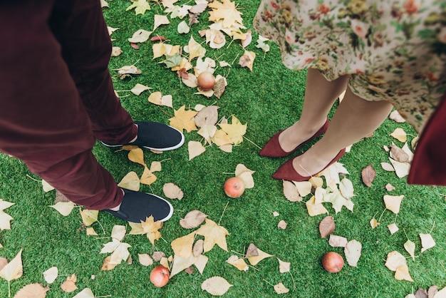 Vue recadrée du couple homme et femme amoureux debout en plein air avec des feuilles d'automne sur fond. concept de mode de vie et de relations
