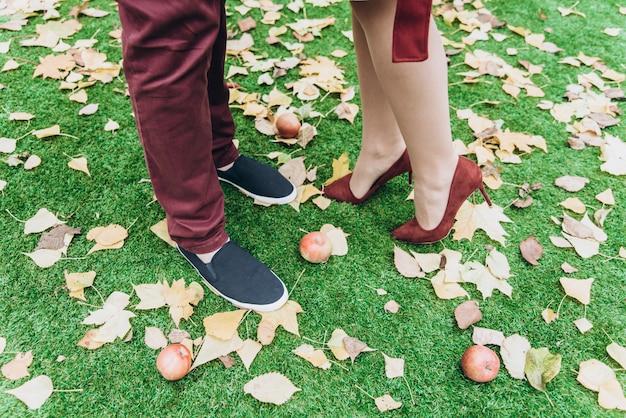 Vue recadrée du couple homme et femme pieds amoureux romantique en plein air avec des feuilles d'automne sur fond. concept de mode de vie et de relations