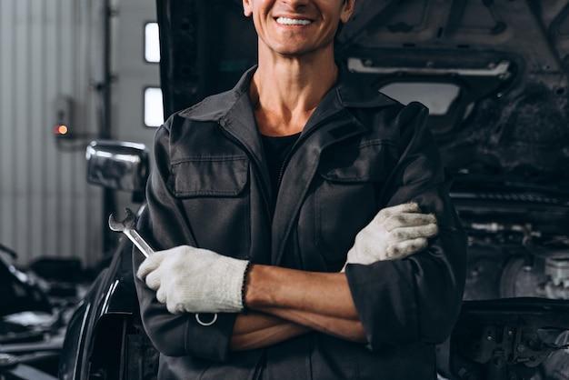 Vue recadrée du mécanicien automobile debout près d'une voiture ouverte à l'extérieur et tenant une clé. concept de réparation de voiture