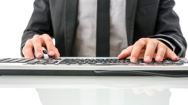 Vue recadrée du travailleur en costume assis à son bureau à l'aide d'un ordinateur.