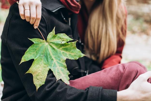 Vue recadrée des époux amoureux assis sur la nature automnale dans un parc et s'embrassant tout en profitant d'une belle journée d'automne. femme tenant une feuille d'érable