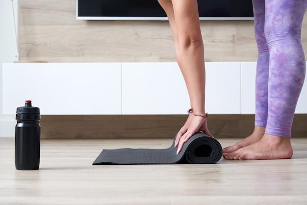 Vue recadrée d'une femme pliant un tapis de yoga ou de fitness noir après s'être entraînée à la maison dans le salon