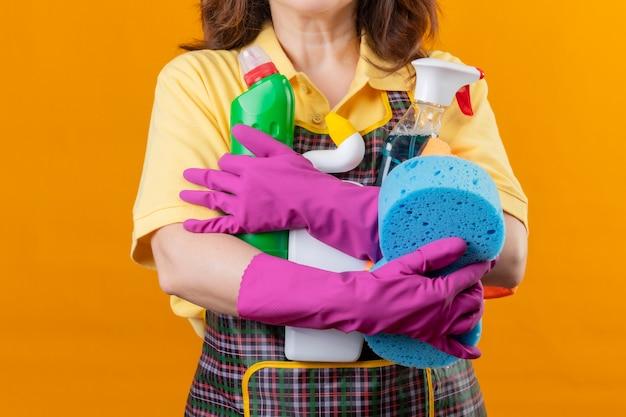 Vue recadrée de femme portant un tablier et des gants en caoutchouc tenant des outils de nettoyage debout sur fond orange isolé