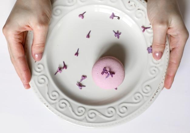 Vue recadrée d'une femme tenant une assiette avec un délicieux macaron français rose ou un macaron aux fleurs lilas sur fond blanc.