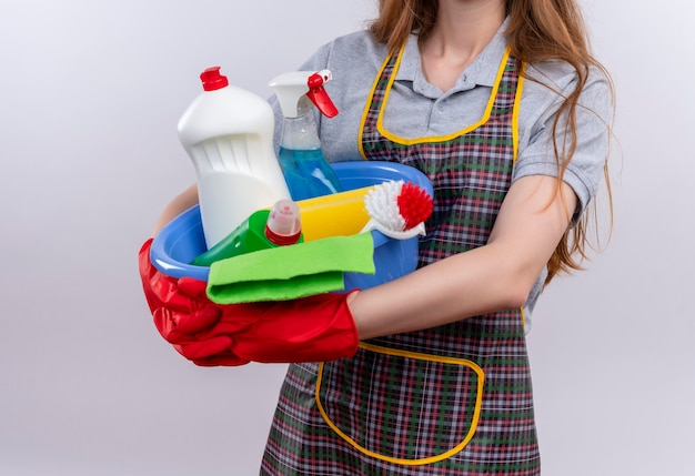 Vue recadrée de fille en tablier et gants en caoutchouc tenant le bassin avec des outils de nettoyage