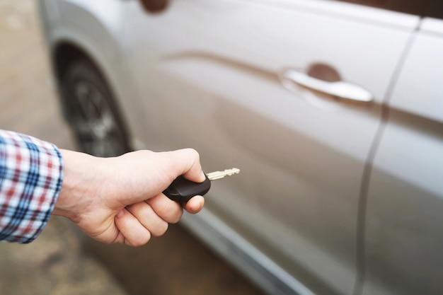 Vue recadrée de gros plan d'une main de l'homme en insérant la clé dans la serrure de porte d'une voiture