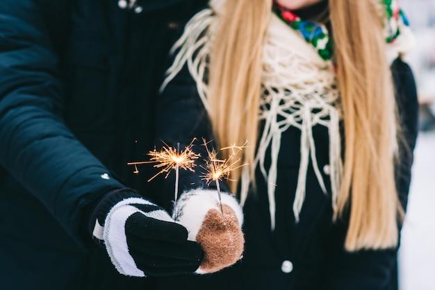Vue recadrée de l'heureux couple d'amoureux admirant la météo hivernale dans le parc. ils se font des câlins et se lient tout en tenant des étincelles