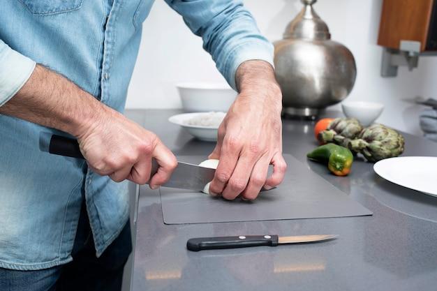 Vue recadrée de l'homme coupe légumes sur planche à découper à la cuisine