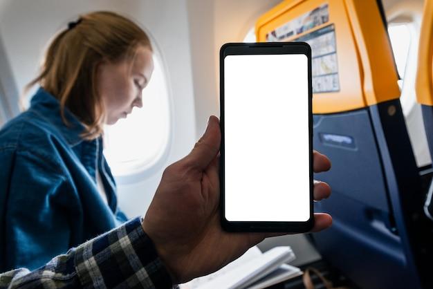 Vue recadrée de l'homme méconnaissable assis sur une chaise dans l'avion et montrant l'écran d'un smartphone. la fille est à l'arrière-plan