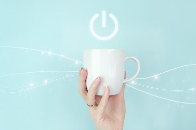 Vue recadrée de la main féminine avec une tasse à café blanche et une icône de bouton de signe sur fond bleu. démarrez le concept d'entreprise. concept de mise sous tension.