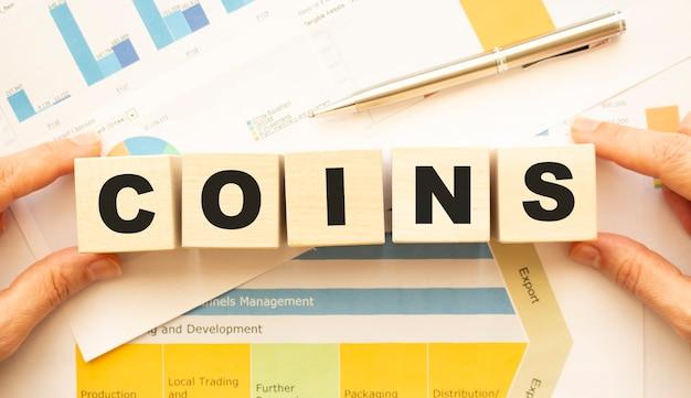 Vue recadrée des mains tenant des cubes en bois avec des pièces de monnaie sur la table de travail