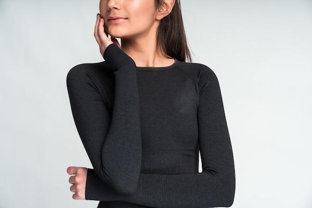 Vue recadrée de la sérieuse femme asiatique aux cheveux noirs posant au studio contre un mur blanc après l'entraînement. concept de mode de vie sain, de sport et d'entraînement