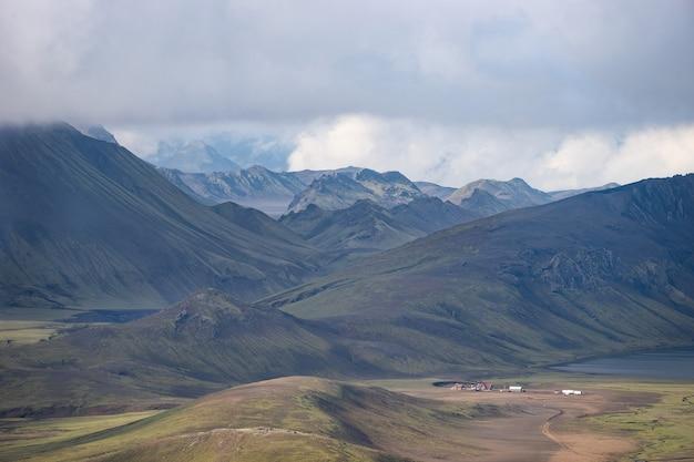 Vue sur le refuge de hvanngil et le camping avec collines verdoyantes, ruisseau et lac. sentier de randonnée laugavegur, islande.