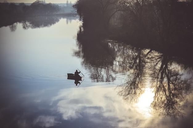 Vue sur la rivière et la silhouette d'un pêcheur dans un bateau naviguant, filtre ou effet