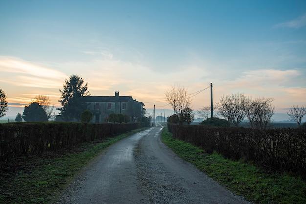 Vue d'une route sale générique dans le paysage de campagne en saison d'hiver