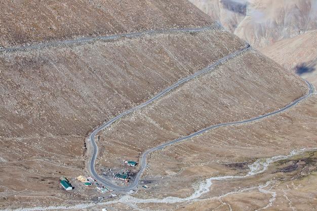 Vue sur route sinueuse et montagnes rocheuses majestueuses dans l'himalaya indien, région du ladakh, inde. concept de nature et de voyage