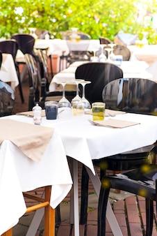 Vue de la rue d'une terrasse de café avec des tables et des chaises.