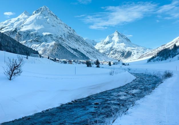 Vue sur le ruisseau de montagne d'hiver et village dans la vallée de l'autriche.