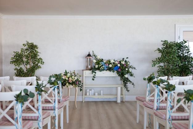 Vue d'une scène de cérémonie de mariage dans une pièce avec plusieurs rangées de chaises blanches et des compositions