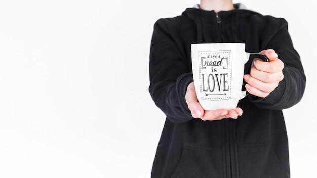 Vue de la section médiane d'une personne tenant une tasse blanche avec tout ce dont vous avez besoin est le texte d'amour