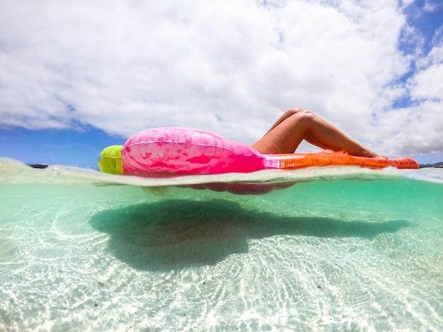 Vue sous-marine de belle femme de race blanche profitant des vacances d'été de détente sur un lilo tendance de couleur dans la mer des caraïbes transparente - les gens ayant un bain de soleil à la plage tropicale