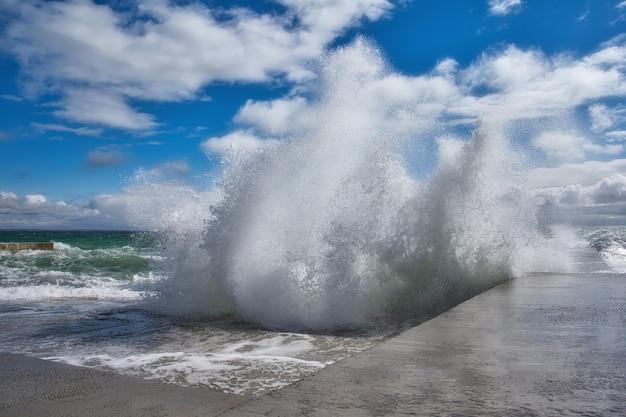 Vue spectaculaire des vagues de la mer s'écrasant contre la jetée en béton