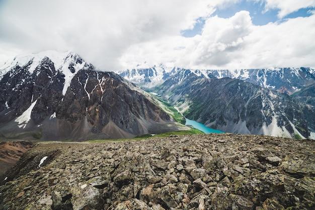 Vue spectaculaire sur la vallée pittoresque avec grand beau lac de montagne entouré de chaînes enneigées géantes et de glaciers.