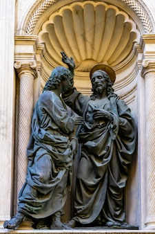 Vue sur les statues du christ et de saint thomas par andrea del verrocchio, à l'extérieur de l'église orsanmichele à florence, italie