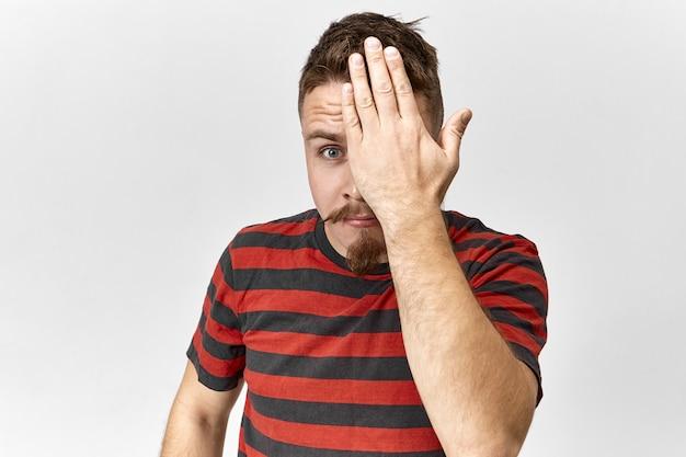 Vue de studio isolé de beau jeune homme élégant avec chaume et moustache gardant une main sur son œil et regardant la caméra, ayant un sourire ludique, se sentant timide. un mec barbu vous espionne