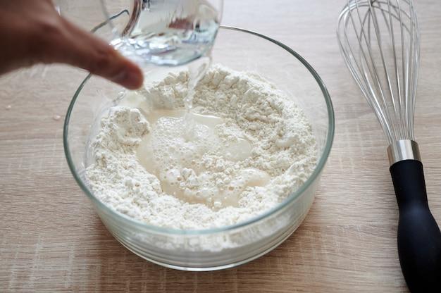 Vue subjective de la main versant de l'eau sur un récipient en verre avec de la farine, avec un placage agité à côté