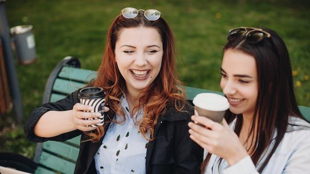 La vue supérieure d'une dame caucasienne dodue souriant près de son amie tout en buvant un café chaud sur un banc dans le parc